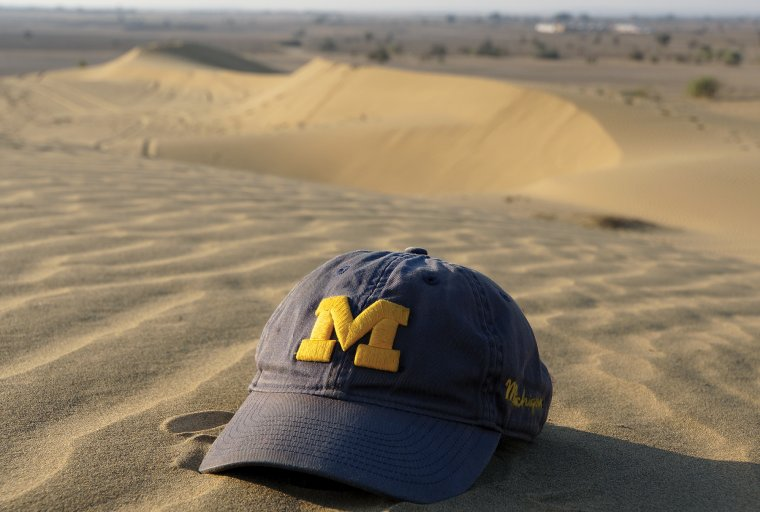 Michigan cap on a desert sand dune