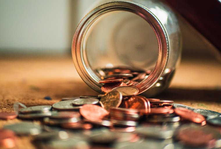 Coin money being spilled out of a jar