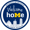 "Blue circle with ""Welcome Home"" written in the middle above the skyline of the Michigan Union"