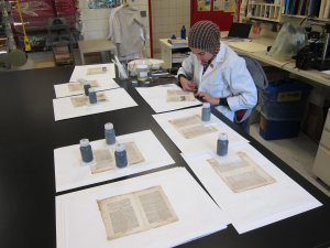 Aisha Wahab, paper conservator, mends pages in the U-M Library Conservation Lab