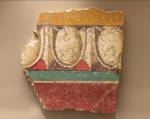 A fragment of a fresco (a type of wall painting) found in the ancient Roman city of Pompeii. Delicately painted, this painting shows a design called egg and dart. Oval egg shapes are interspered with vertical lines and painted to give the painting a sense of depth even though it is flat. Brightly colored bands decorate the fragment, which is about the size of an adult's hand, above and below the egg and dart pattern.