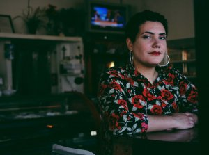 Photograph of poet Raquel Salas Rivera wearing a floral shirt and hoop earrings
