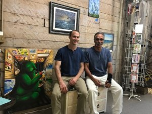 two men sit facing the viewer in front of artwork being installed on a wall