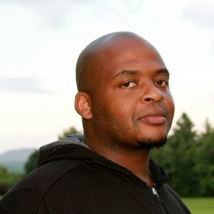 Author Kiese Laymon, an African American man with a shaved head wearing a black zippered shirt.