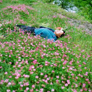 Photograph by Park Young Sook, The Madwomen Project: A Flower Shakes Her (2005). Description of image: A woman wearing blue shirt and navy pants is lying on a bed of pink wildflower in bloom, with her eyes closed and a slight smile on her face.
