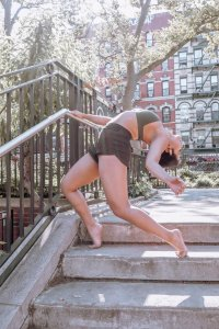 Dancer poses in a backbend on the concrete steps of a sunny park.