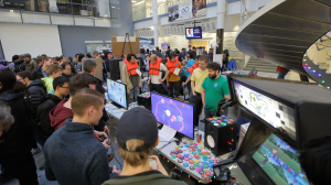 A large crowd plays new student-made video games at the EECS 494 + EMU Showcase