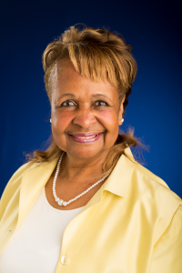 Wendy Woods - older African American woman with short blonde hair, smiling, wearing yellow collared shirt, white necklace, and white shirt underneath.