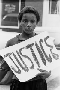 """Women at march holding a """"Justice"""" sign"""