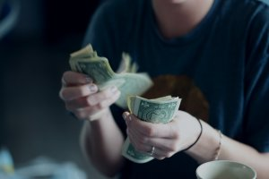 woman counting dollar bills.