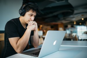 Student with headphones on and hands near face looking at laptop screen