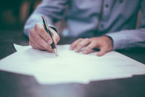 person signing documents on table