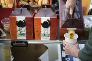 Three Panera box shaped coffee jugs in a row labled left to right, hot h2o, decaf, and coffee. A hand is pictured pouring coffee from the right most jug into a coffee cup that the person is holding. The jugs are on a table with bagels in baskets in the background.
