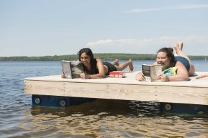 Two students read books for class on the floating dock in Douglas Lake.