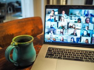 photo of coffee cup and computer with zoom meeting