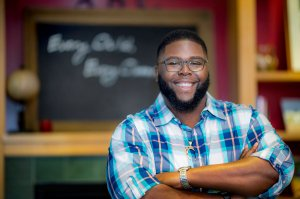Anthony Abraham Jack, an african-american man with a full beard and glasses, smiles, standing with crossed arms in front of a blackboard.