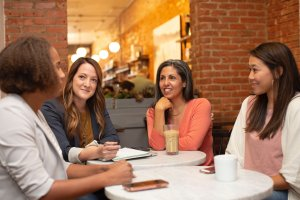 4 women around a table talking and networking