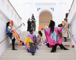 A group of performers hold cut outs of colorful geometric shapes on the stairway of a museum while two audience members look on.