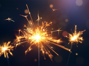 Three lit sparklers with a black background
